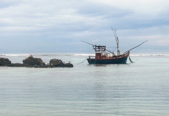 a fishing boat in the distance / weligama is primarily a fishing town