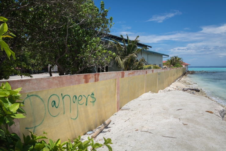 Graffiti on a boundary wall warns of things that lie ahead on Maafushi's northern end.