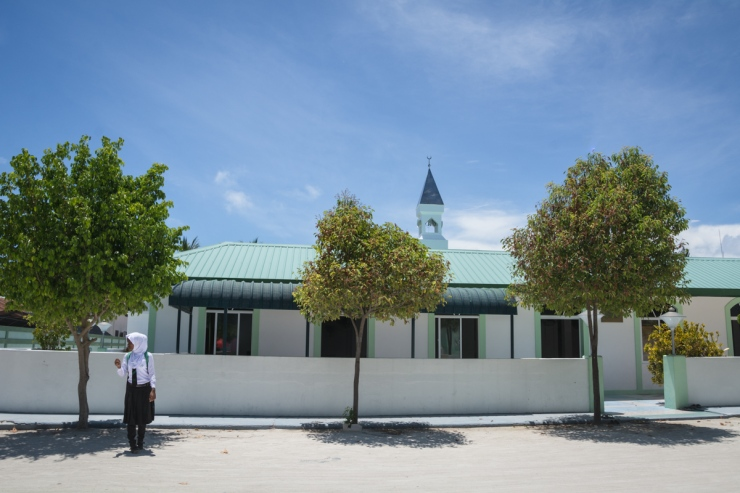 A schoolgirl waits in front of one of the island's two mosques. Many girls in Maafushi nowadays work in the hospitality industry as receptionists.