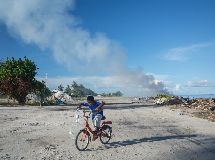 A local boy returns home after picking out discarded plastic bottles from the burning trash pile behind him. He intends to use them as fishing reels, a practice that developed as plastic became widespread with the rise of tourism.