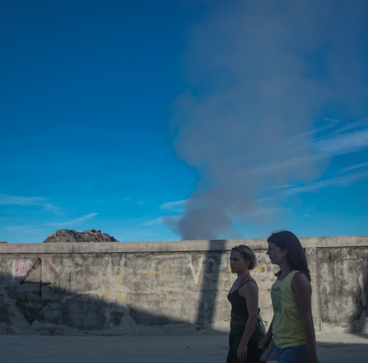 Two tourists walk past a wall behind which a mound of garbage has been set on fire. Garbage is traditionally burnt all over the Maldives due to the lack of landfill space on the little islands, and with the growth of tourism in Maafushi, trash is now as ubiquitous as foreign visitors.