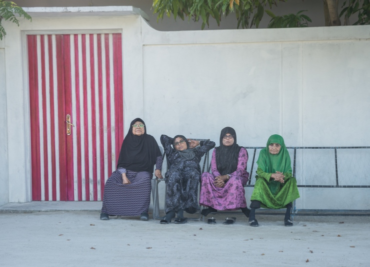 Elderly women lounge outside on traditional jolis on a residential alleyway.