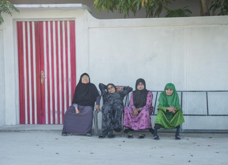 Elderly women lounge outside on traditional jolis on a residential alleyway.