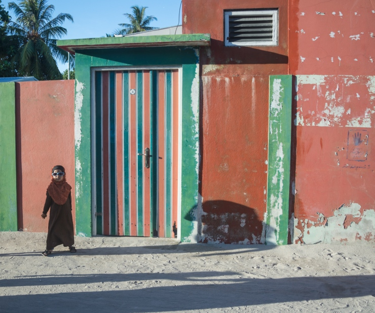 A young Maafushi resident in shades strikes a quick pose for the camera.