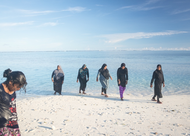 Maldivian women walk out of the water after a customary half-immersed rendezvous.