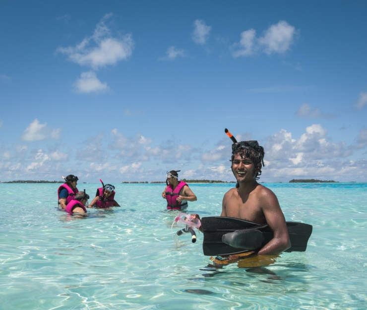 Tourists prepare to snorkel under Ahmed's watch. Ahmed grew up in Maafushi and now works as a snorkelling guide with a local family-run tour company.