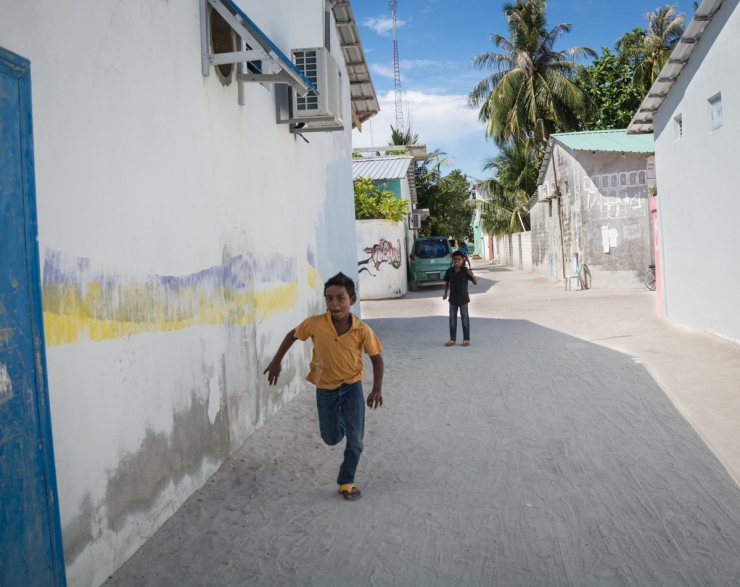 Two boys in a residential alleyway. With the higher income generated from small-business tourism, ACs and cars are becoming a common sight.