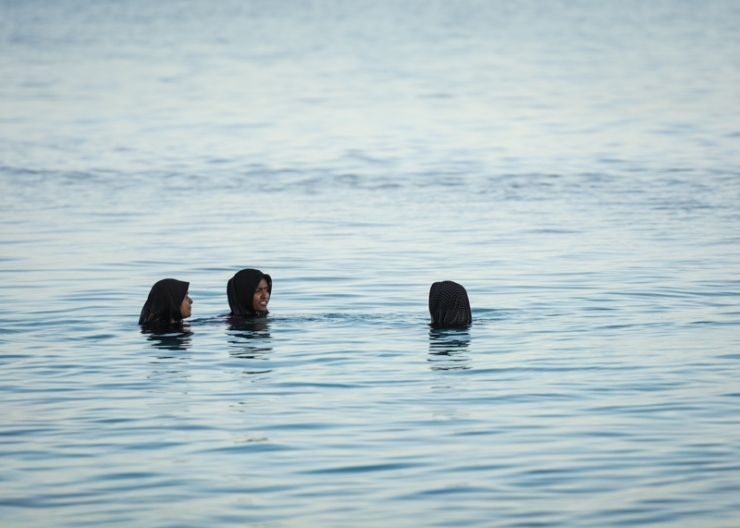 Three Maafushi women have an afternoon chat in the customary island style. While navigating sea water is a way of life for Maldivians, climate change poses a grave threat to these islanders, whose country is expected to disappear under water by the end of the century. Several islands, including Maafushi, are already shrinking due to erosion caused by excessive development, much of which is tourism-related.